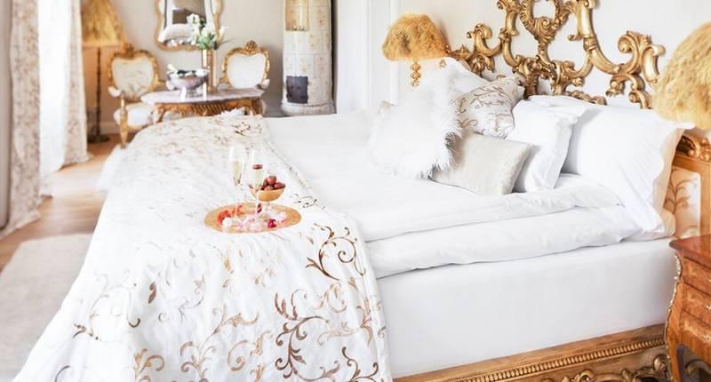En romantisk säng i ett vackert rum på ett Slott. Med champagne och jordgubbar på en bricka vid sängen.