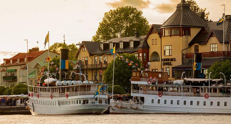 Hotell vid havet och skärgårdsbåtar vid kajen