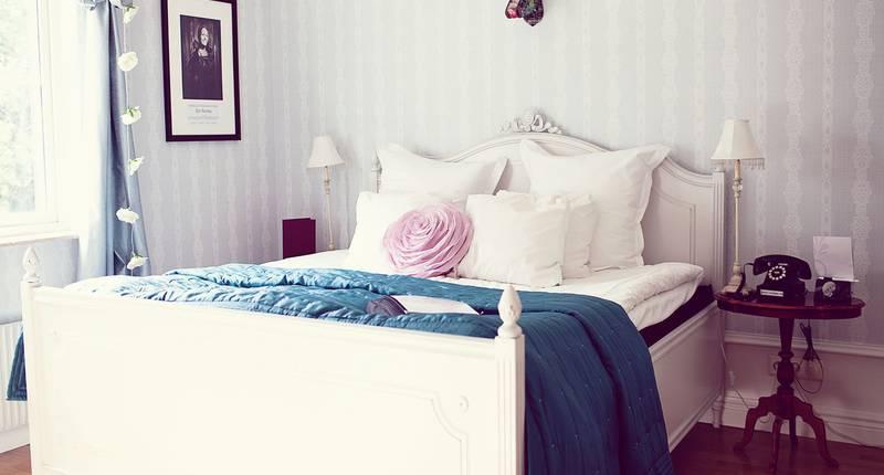 Mysigt rum på ett hotell i Art Deco stil. En säng med en ros.